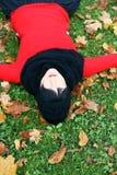 Ung brunettkvinna som kopplar av i höstparken Arkivfoto