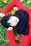 Ung brunettkvinna som kopplar av i höstparken Royaltyfria Foton