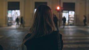 Ung brunettkvinna som korsar trafikvägen i aftonen och går i stadsmitten bara, till och med gatorna arkivbild