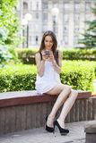 Ung brunettkvinna som läser ett meddelande på telefonen arkivbilder