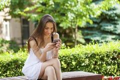 Ung brunettkvinna som läser ett meddelande på telefonen royaltyfri bild