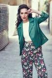 Ung brunettkvinna som ler i stads- bakgrund Royaltyfria Bilder