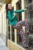 Ung brunettkvinna som ler i stads- bakgrund Arkivfoto