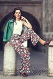 Ung brunettkvinna som ler i stads- bakgrund Royaltyfria Foton