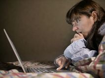Ung brunettkvinna som ligger p? s?ngen och arbetar i hennes b?rbar dator royaltyfria foton