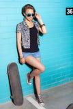 Ung brunettkvinna som poserar med skateboarden royaltyfria bilder