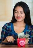 Ung brunettkvinna som sitter vända mot ner kameran, genom att använda på räknemaskin- och innehavbunten av dollarräkningar, rosa  Fotografering för Bildbyråer