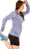 Ung brunettkvinna som sträcker dra upp ett ben Arkivfoto