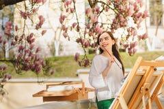 Ung brunettkvinnakonstn?r som rymmer i h?nder en borste och en palett N?ra henne magnoliatr?det och den olika konstutrustningen arkivbild