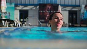 Ung brunettkvinnasimning i pölen arkivfilmer