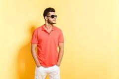 Ung brunettman i solglasögon som poserar att se bort Arkivfoto
