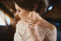 Ung brunettskönhet med att gifta sig frisyren i innegrej snör åt klänningen som justerar hennes örhänge och poserar på inre arkivbild