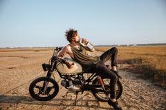 Ung brutal man som lägger på hans motorcykel och dricksvatten Royaltyfri Fotografi