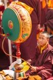 Ung buddistisk munk med en stor rituell vals arkivfoto