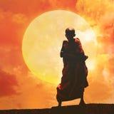 Ung buddistisk munk på orange solnedgång Arkivbilder