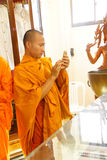 Ung buddistisk munk som kontrollerar mobiltelefonen Royaltyfria Foton