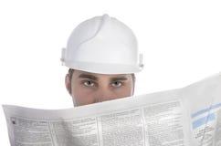 Ung byggnadsarbetare som studerar tidningen för jobb royaltyfri fotografi