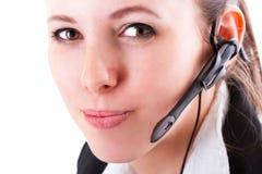 Ung call centeranställd med en hörlurar med mikrofon Arkivbild