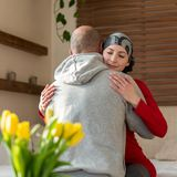 Ung cancerpatient för vuxen kvinnlig som hemma kramar hennes make efter behandling i sjukhus Cancer- och familjservice royaltyfria bilder