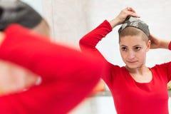 Ung cancerpatient för vuxen kvinnlig som justerar hennes sjalett som ser i spegeln Trött, utmattad deprimerad cancerpatient Royaltyfria Bilder