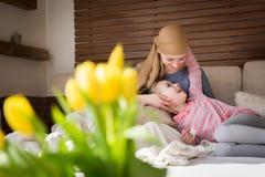 Ung cancerpatient för vuxen kvinnlig som spenderar tid med hennes hemmastadda dotter och att koppla av på soffan Cancer- och fami royaltyfri fotografi
