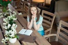 Ung caucasian affärskvinna i kafésammanträde på tabellen med fundersam stirrande royaltyfri fotografi