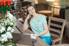 Ung caucasian affärskvinna i kafésammanträde på tabellen med fundersam stirrande arkivfoto