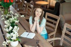 Ung caucasian affärskvinna i kafésammanträde på tabellen med fundersam stirrande arkivbild