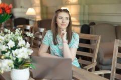 Ung caucasian affärskvinna i kafésammanträde på tabellen med fundersam stirrande arkivfoton