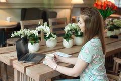 Ung caucasian affärskvinna i kafésammanträde på tabellen med fundersam stirrande royaltyfria foton