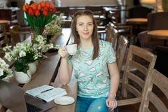 Ung caucasian affärskvinna i kafésammanträde på tabellen med fundersam stirrande fotografering för bildbyråer