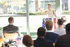 Ung Caucasian affärskvinna som gör anförande till affärsfolk i konferensrum royaltyfria foton