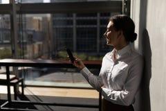 Ung Caucasian affärskvinna som lutar mot väggen och i regeringsställning använder mobiltelefonen arkivfoton