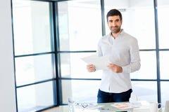 Ung caucasian affärsman som i regeringsställning står royaltyfri bild