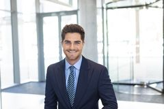 Ung Caucasian affärsman som ler på kameran, medan stå i modernt kontor fotografering för bildbyråer