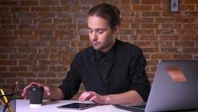 Ung caucasian affärsman som nallar hans apparat och dricker kaffe, medan sitta på skrivbordet nära den kopplade av datoren lager videofilmer