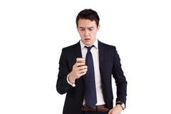 Ung Caucasian affärsman som rynkar pannan se mobiltelefonen Fotografering för Bildbyråer