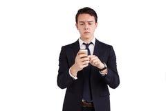 Ung Caucasian affärsman som rynkar pannan se mobiltelefonen Arkivbilder