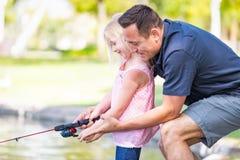 Ung Caucasian fader och dotter som har roligt fiske på laen Royaltyfri Bild