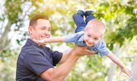 Ung Caucasian fader och son som har gyckel på parkera Arkivbild