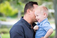Ung Caucasian fader och son som har gyckel på parkera Arkivfoton