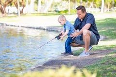 Ung Caucasian fader och son som har roligt fiske på sjön Arkivfoto