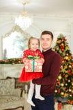 Ung caucasian fader som håller den lilla dottern med gåva, julgran i bakgrund Fotografering för Bildbyråer