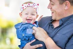 Ung Caucasian fader Tickles Baby Girl på parkera Royaltyfri Fotografi