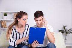 Ung Caucasian familj som har skuldproblem som inte ?r i st?nd till att betala ut deras l?n Kvinnlig, i exponeringsglas och att st royaltyfria foton
