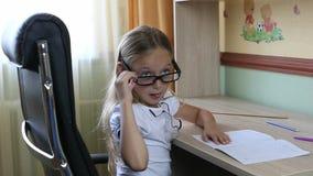 Ung caucasian flicka i exponeringsglas som sitter på stol vid tabellen Stäng sig inomhus upp sikt på nätt flicka i exponeringsgla Royaltyfri Fotografi