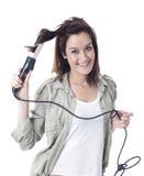 Ung caucasian flicka som använder krullande järn Arkivbild