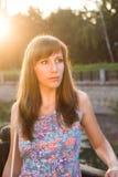 Ung caucasian flicka som drömmer i solnedgångljus Arkivbilder