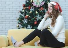 Ung caucasian i den röda hatten som sitter på soffan mellan jultre royaltyfria bilder