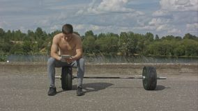 Ung caucasian idrottsman som använder hans minnestavladator efter det utomhus- drevet Royaltyfria Foton